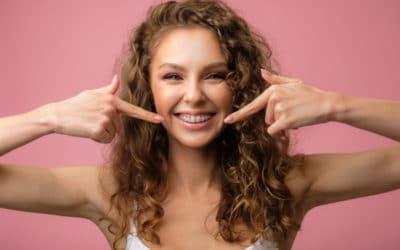 Junge Frau laechelt und zeigt mit ihren Fingern auf ihre feste Zahnspange