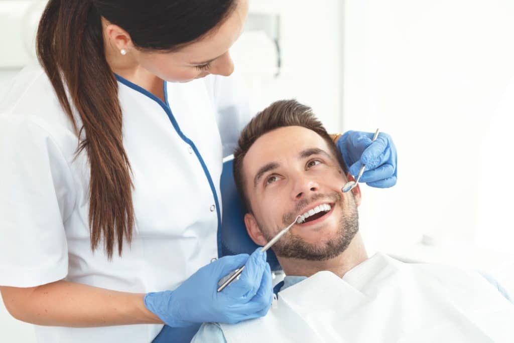 Junger Mann wird zum letzten mal nach dem entfernen einer Zahnspange kontrolliert