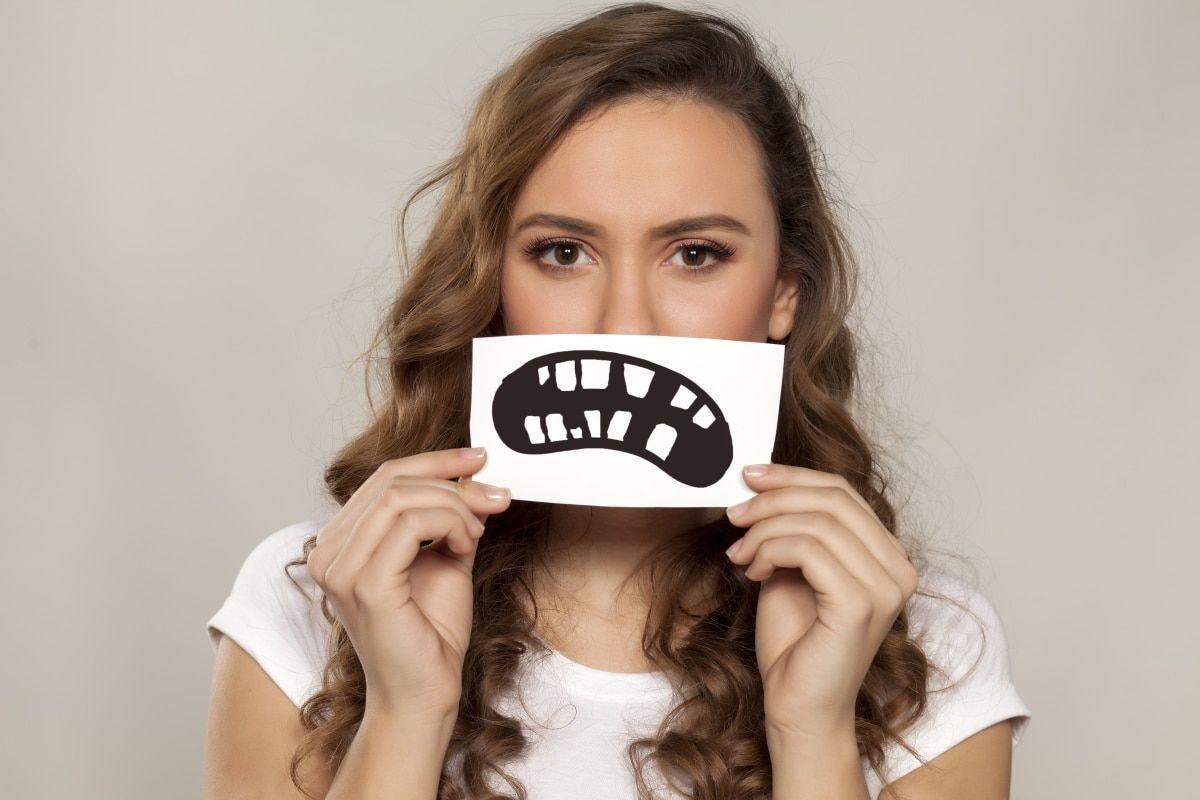 Frau hält ein Bild vor den Mund mit sehr schiefen Zähnen