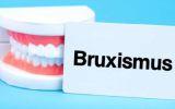Ein Schild mit der Aufschrift Bruxismus lehnt an einem Modellgebiss