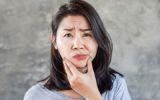 Eine Frau hält ihren schiefen Kiefer fest und verzieht schmerzend das Gesicht