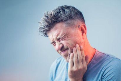 Ein Mann hält sich die Hand an den Kiefer aufgrund von Schmerzen