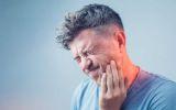 Ein Mann hält sich die Hand an den Kiefer aufgrund von Schmerzen im Kiefergelenk