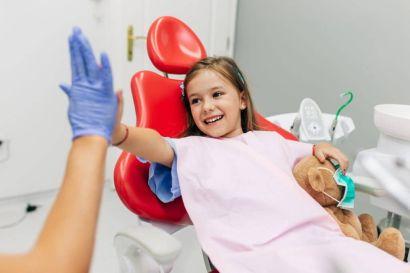 kleines Mädchen klatscht glücklich nach der Behandlung