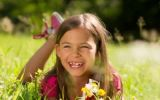 Kind liegt auf der Wiese und lächelt mit sehr schiefen Zähnen
